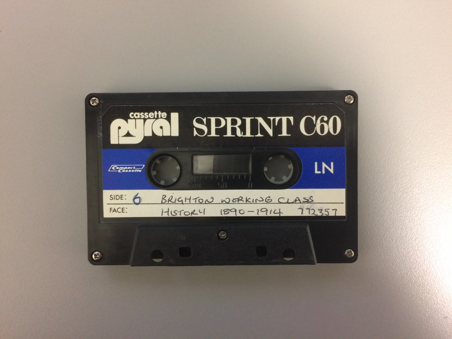 A black compact cassette tape with a white and blue label.