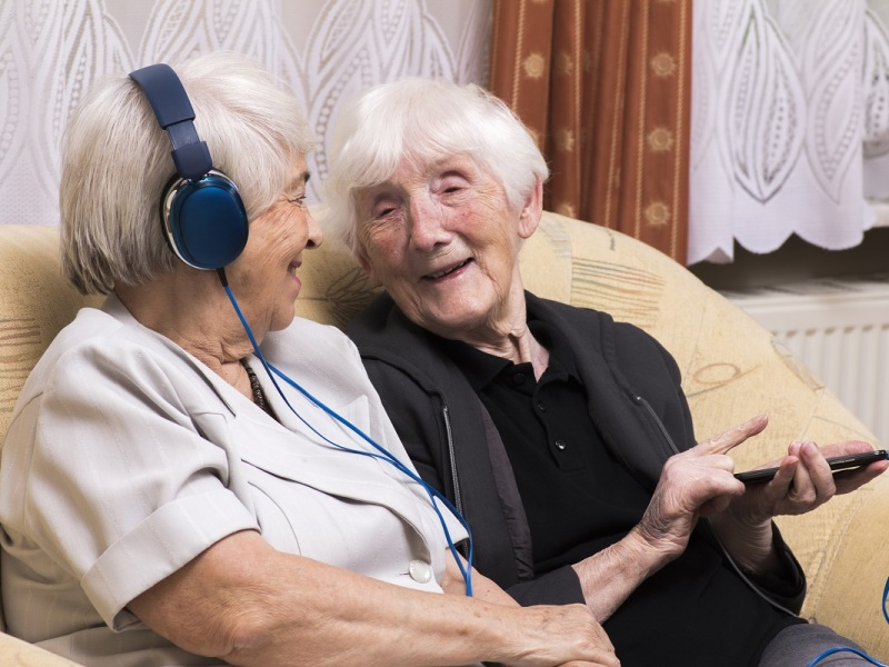 Two women, sitting on a sofa. One is wearing headphones, the other is holding a mp3 player. Both are smiling.