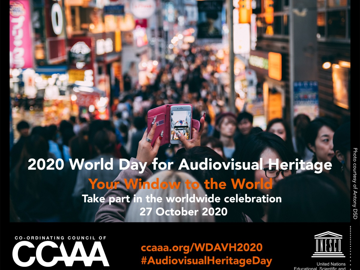 A camera phone is held up to photograph a busy road scene. The text reads 2020 World Day for Audiovisual Heritage Your Window to the World.