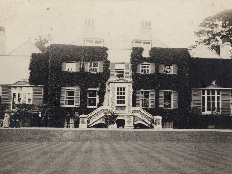 Black and white image of an ivy-covered large house.
